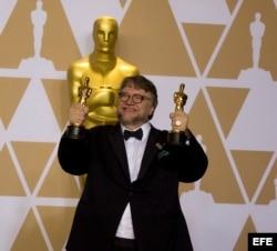 Guillermo del Toro muestra sus dos estatuillas por mejor director y mejor película.