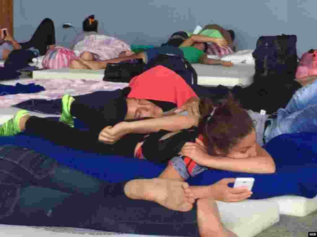 Cubanos varados en Costa Rica, teléfono en mano.