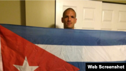 Osvaldo Ozzie Alonso Moreno, sostiene una bandera cubana.