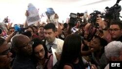 """Los opositores cubanos Manuel Cuesta Morúa (i) y Lilianne Ruiz (c) son hostigados por miembros de la delegación oficialista cubana a la entrada del """"Foro de la sociedad civil y actores sociales"""" de la VII Cumbre de las Américas."""
