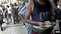 Un hombre cuenta dólares frente a una Casa de Cambio.