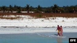 Una pareja de turistas camina por playa Sirena, en Cayo Largo del Sur.