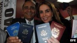 La periodista venezolana Lourdes Ubieta, acompañada de Carlos Herrades, muestran sus dos pasaportes, de Venezuela y Estados Unidos.