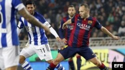 Delantero mexicano de la Real Sociedad Carlos Vela (i) lucha un balón con Andrés Iniesta.