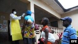 Una enfermera monitorea la temperatura de varias personas en el condado de Bomi, Liberia.