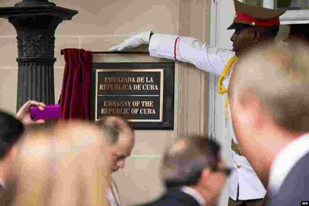 Un miembro de la guardia de honor descubre la placa que acredita al edificio como la embajada embajada del país en Washington.