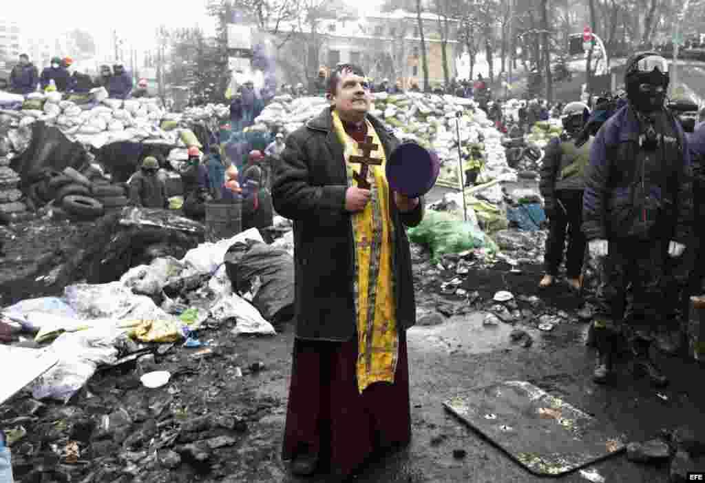 Un sacerdote ucraniano reza ante una barricada en otra jornada de protestas antigubernamentales en Kiev (Ucrania) .