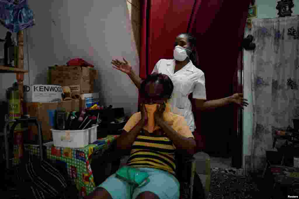 Hairdresser Yulieska Iglesias, wearing a protection mask amid concerns about the spread of the coronavirus disease (COVID-19), gestures after finishing with a client at her home, in Havana, Cuba, March 25, 2020. REUTERS/Alexandre Meneghini