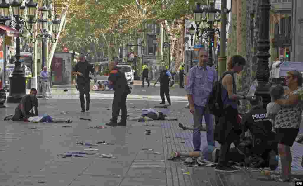 Varias víctimas en el suelo en el lugar del atropello masivo realizado por una furgoneta que ha arrollado esta tarde a varios viandantes que paseaban por las Ramblas de Barcelona. Los Mossos d'Esquadra y los equipos de emergencias sanitarias han desplega