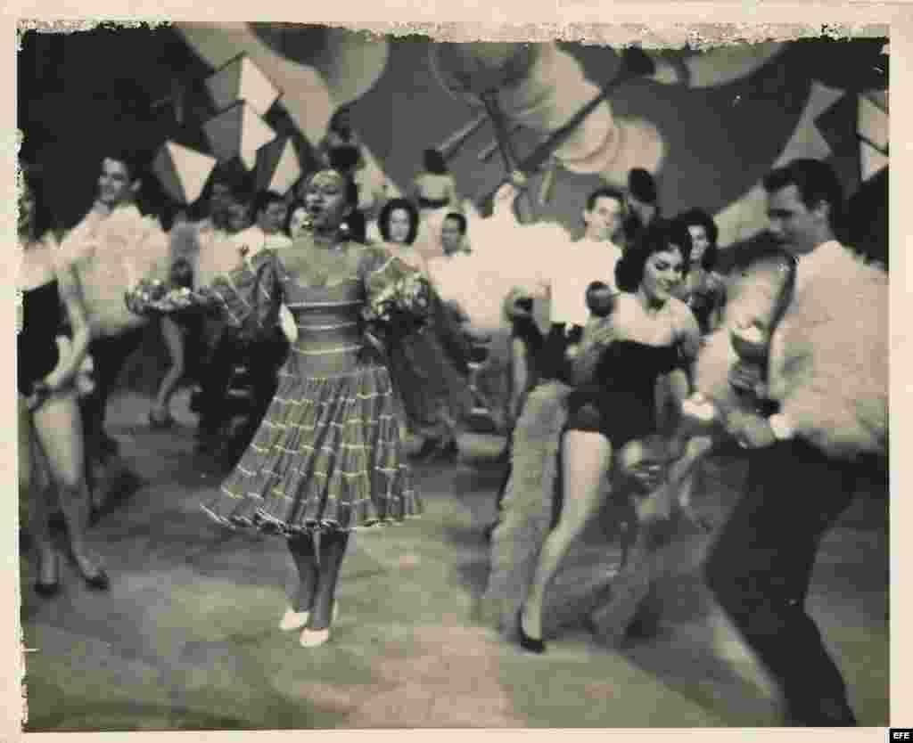 Celia Cruz durante la década de los años 50, con un traje azul de algodón en la presentación de una revista musical.
