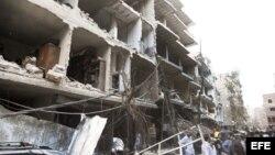 Fotografía cedida por la agencia de noticias SANA que muestra a unos ciudadanos sirios en el lugar donde se registró la explosión de un coche bomba en el barrio de Def al Shuk en Damasco, Siria.