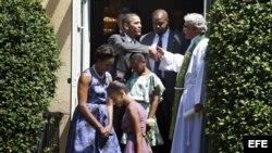 Barack Obama se despide del reverendo Luis León (d) tras asistir al servicio religioso junto a su esposa Michelle Obama (i) y sus hijas Malia (2i) y Sasha (3d)