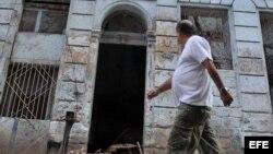Un hombre camina frente a un edificio que se derrumbó parcialmente debido a las fuertes lluvias y que se encuentra ubicado en el barrio de Centro Habana, en La Habana (Cuba).