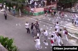 Damas de Blanco lanzan octavillas antes de ser detenidas por la policía.