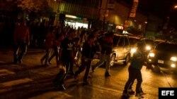 Transeúntes circulan por una calle en la oscuridad durante un corte de energía eléctrica en Caracas (Venezuela).