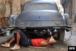 Un hombre trabaja en la reparación de un auto.