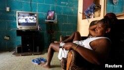 Una mujer descansa en su sofá mientras la televisión transmite una sesión de la Asamblea Nacional.