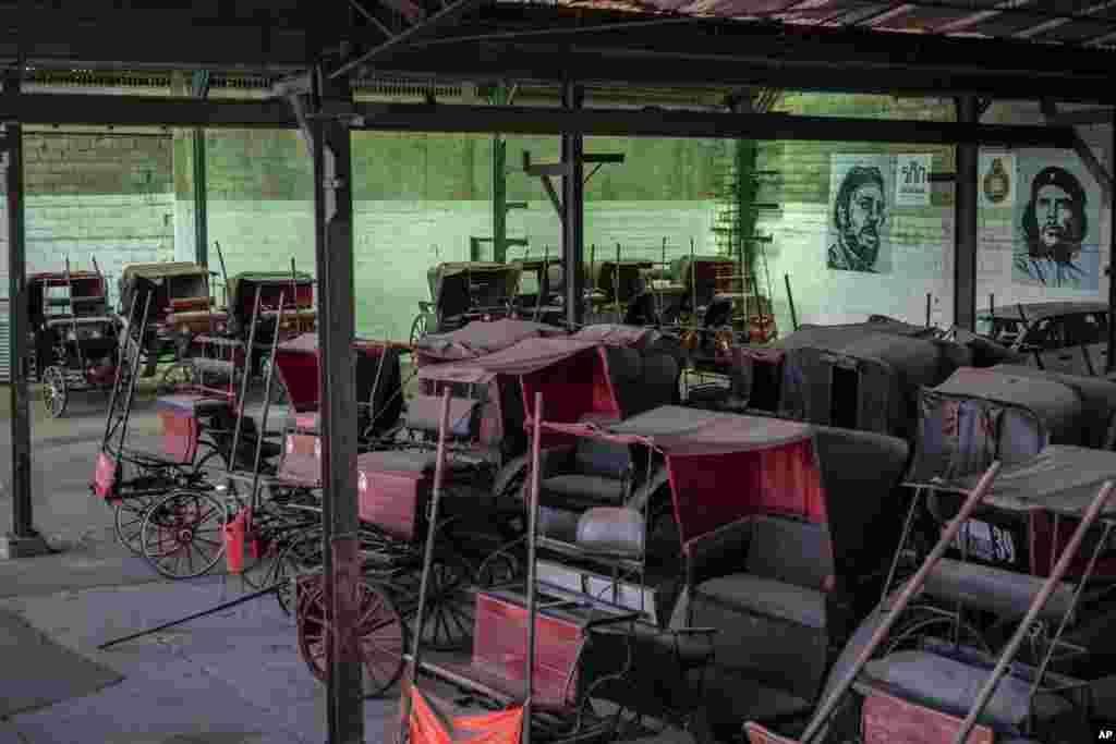 """Los carros de caballos que solían dar paseos a los turistas permanecen inactivos en el garaje de una cooperativa donde los murales del difunto líder Fidel Castro y el héroe revolucionario Ernesto """"Che"""" Guevara cubren las paredes en La Habana, Cuba, el 24 de febrero de 2021."""