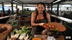 Una mujer vende vegetales en un mercado agropecuario de La Habana.