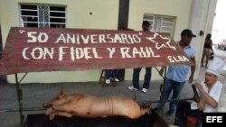 Un hombre cocina un cerdo hoy, en el portal de un edificio, en La Habana Vieja (Cuba)