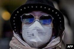 La puerta de acceso al andén se refleja el viernes en las gafas de un pasajero que lleva máscara en una estación ferroviaria de Pekín (Foto: Nicolas Asfouri/AFP).