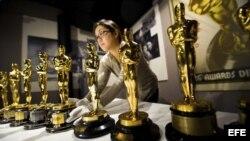 Una mujer coloca los premios de la academia de cine estadounidense.