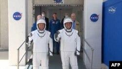 Los astronautas Bob Behnken (derecha) y Doug Hurley se dirigen hacia los vehículos que los transportaron a la rampa de lanzamiento de la cápsula SpaceX Crew Dragon, el 30 de mayo del 2020. (Foto AFP tomada de NASA TV)