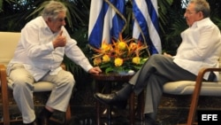 Raúl Castro (d) y el presidente de Uruguay José Mujica (i) hablan durante el encuentro oficial en La Habana.