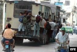 Varias personas viajan colgando de un ómnibus, popularmente conocido como camello
