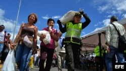 Un policía colombiano ayuda a venezolanos que regresan luego de hacer compras.