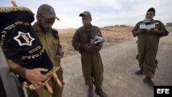Soldado israelíes cargan con una Torá y libros de rezo mientras otros soldados se preparan para desplegarse junto a la frontera con Gaza, en Israel.