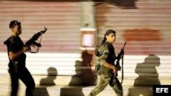 Rebeldes sirios patrullan por las calles de Alepo, Siria.