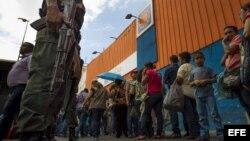 Un grupo de personas aguardan afuera del supermercado Día a Día para ingresar y hacer compras, bajo presencia militar, en la ciudad de Caracas (Venezuela).