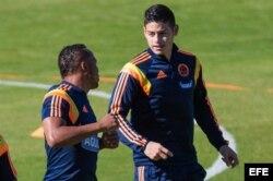 James Rodríguez (d) y Camilo Zúñiga (i) de la selección Colombia participan en un entrenamiento de su equipo en Cotía (Brasil).