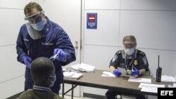 Oficiales de la Oficina de Aduanas y Protección Fronteriza de EEUU interrogan a un viajero y le toman la temperatura.