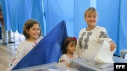 Una ucraniana con sus hijas deposita su voto en las urnas durante las elecciones presidenciales.