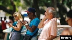 Cubanos conectados a Internet desde un punto WI-Fi en Habana.