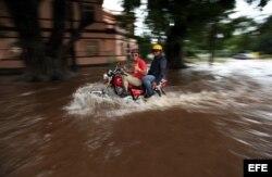 Dos hombres transitan en moto por una calle inundada este viernes 29 de noviembre de 2013, en La Habana