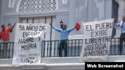 Opositores enarbolan carteles en contra del Gobierno cubano en la catedral de Santiago de Cuba.