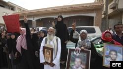 Numerosos familiares de víctimas de la masacre de Abu Salim en el año 1996 muestran retratos de sus parientes, durante una concentración frente a un tribunal que juzga a Abdulá el Senussi, exjefe de inteligencia y cuñado de Muamar el Gadafi, en Trípoli (
