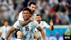 Marcos Rojo (frente) de Argentina celebra con Lionel Messi (arriba) el 2-1 ante Nigeria.