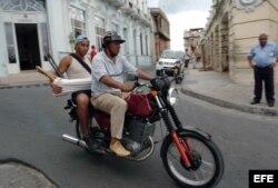 Un motorista lleva en su mototaxi a un pasajero por las calles de Santiago de Cuba.