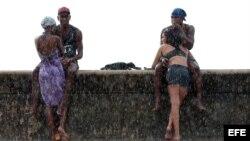 Jóvenes cubanos disfrutan de la lluvia en La Habana. Foto: Alejandro Ernesto.