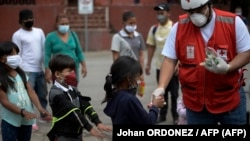 Voluntario de la Cruz Roja entrega alimentos a los niños migrantes hondureños