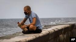 Un hombre echa una rosa al mar en el Malecón de La Habana en medio de la pandemia de coronavirus. (AP/Ramon Espinosa)