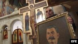Un hombre porta un retrato del exdictador soviético, Joseph Stalin, durante una misa celebrada con motivo del aniversario de su muerte.