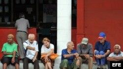 Un grupo de ancianos conversa en la puerta de una bodega en La Habana. EFE/Alejandro Ernesto