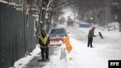 Un obrero retira la nieve acumulada frente a la obra en la que trabaja en Nueva York, Estados Unidos.