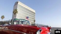 Un auto clásico pasa con una bandera de Estados Unidos frente a la embajada de ese país en La Habana.