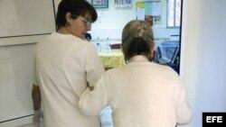 """Una auxiliar acompaña a una enferma de alzheimer en el centro de día """"La Pineda"""" en Castellón, España"""